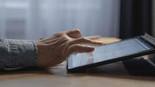 An image of a mans hand touching an ipad screen