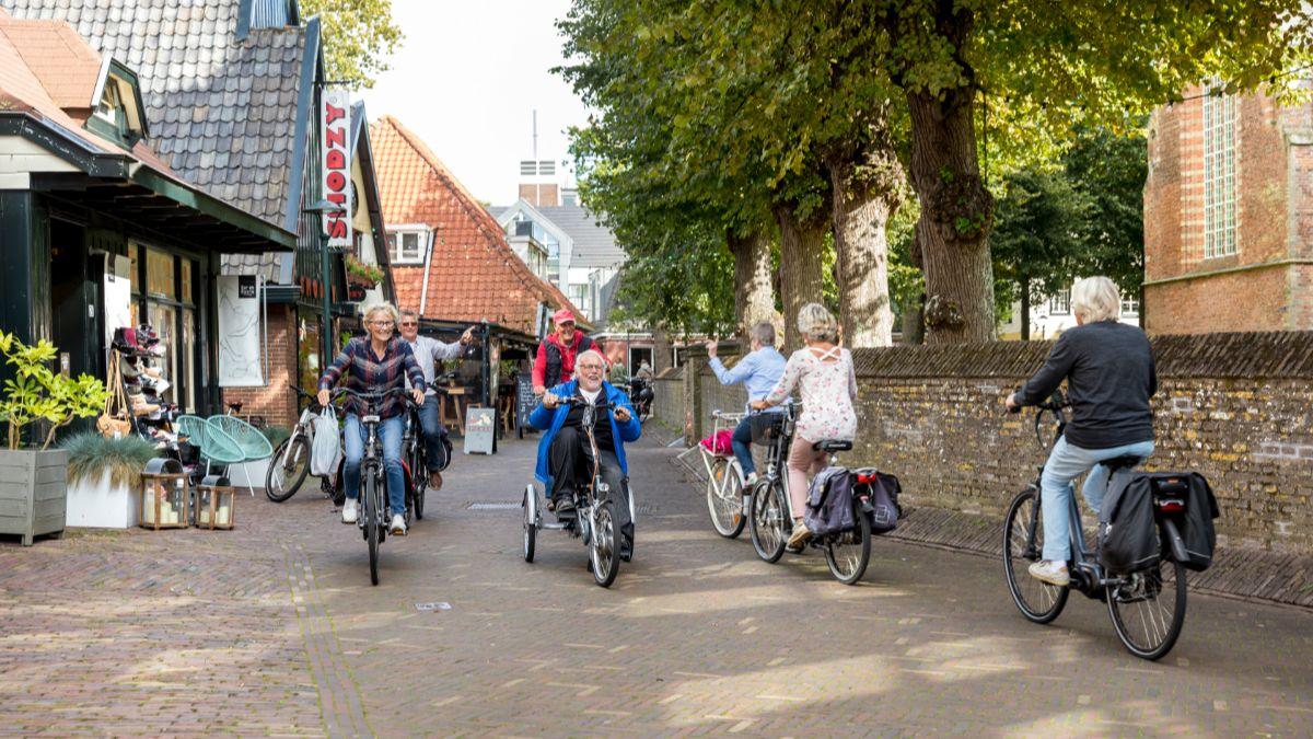 Ouderen op de fiets in dorp