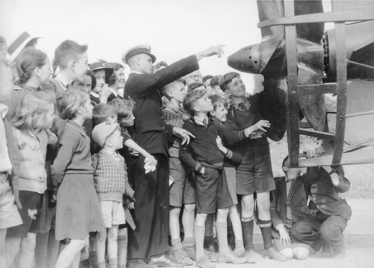 A member of the Royal Australian Navy shows school children a midget submarine which had taken part in the attack on Sydney Harbour 31 May 1942. AWM P00455.016