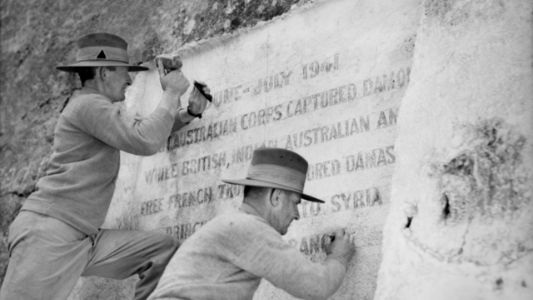 Two men in military uniform carving words on a large memorial stone