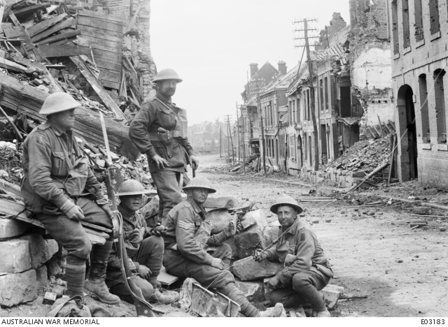 Five Australian soldiers in position with a Lewis gun in a ruined street of Péronne, France, 2 September 1918 AWM E03183