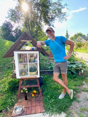 Erik standing next to his garden stand, a quarantine project that he used to maintain connection with neighbors, and continue to connect.