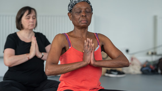 Two women doing a seated yoga position