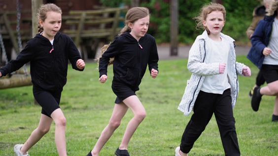 Three young girls running outside