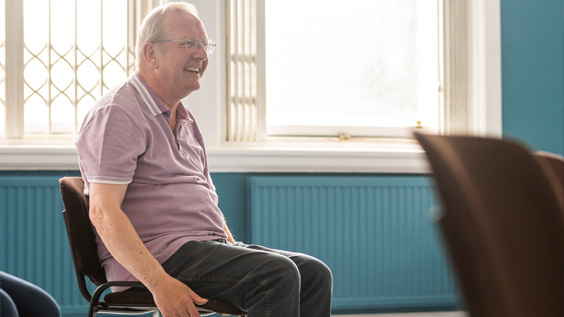 Older man sat in a chair with arms by his side, looking forward and smiling