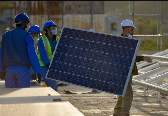 Men carrying solar panels