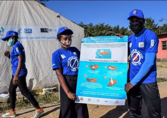 Young people carrying a poster with handwashing instructions