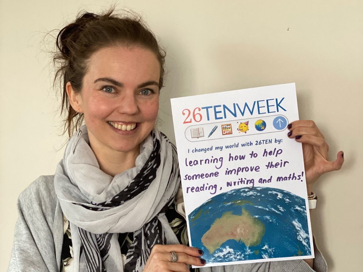 Kate holding a poster that says she changed her world with 26TEN by learning how to help someone improve their reading writing and maths