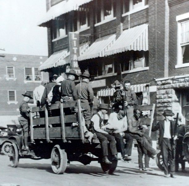 Black and white photo of truck carrying injured after the 1921 Tulsa Massacre.