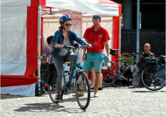 A woman trials an e-bike in front of a Sharing Cities tent centre with a Sharing Cities man assisting