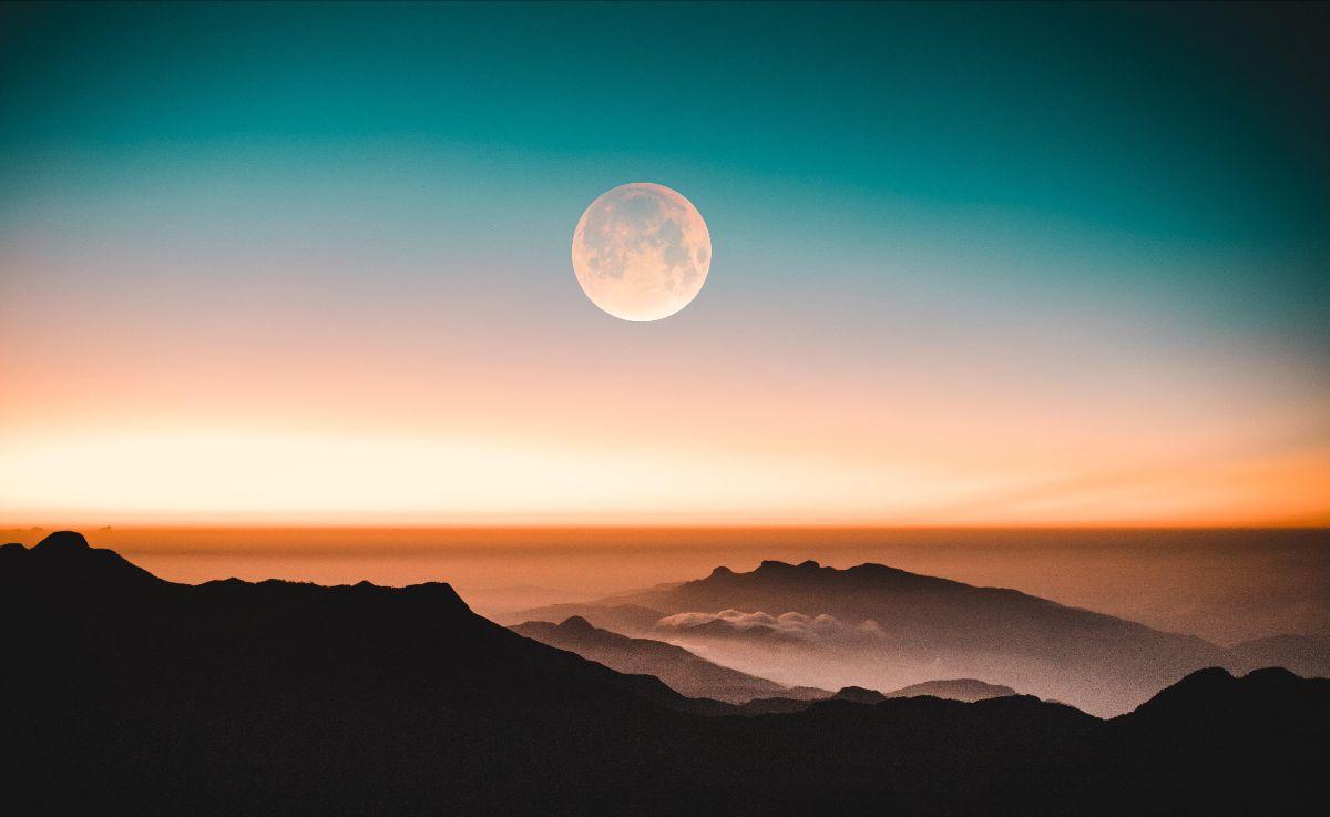 A full moon rises over mountain ridges