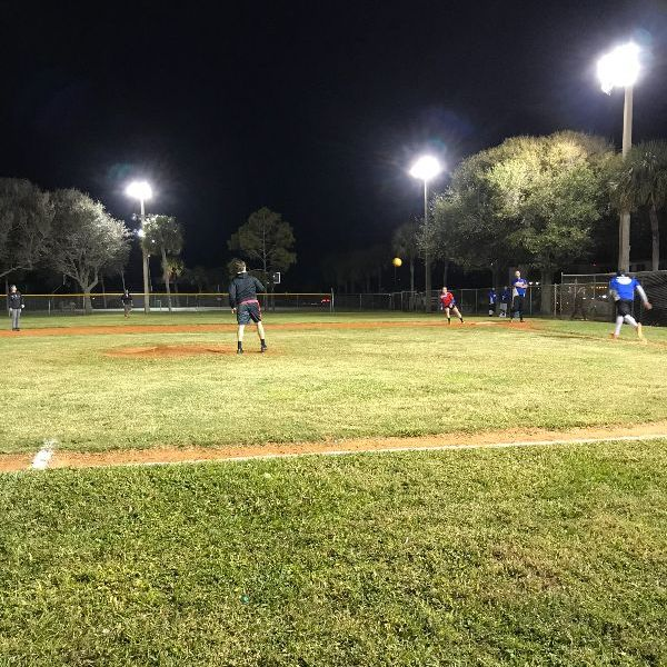 night kickball game under the lights, pitcher throwing ball to first base
