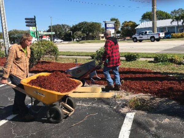 two men pushing wheelbarrows of mulch, outside