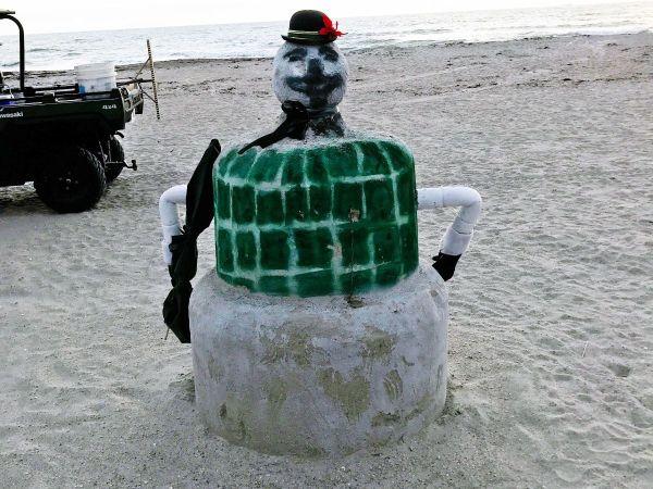 snowman built from sand on the beach