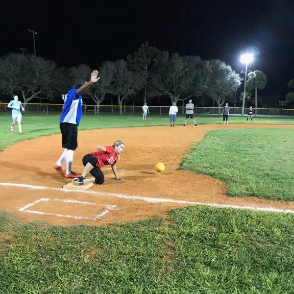 kickball player sliding into base at night