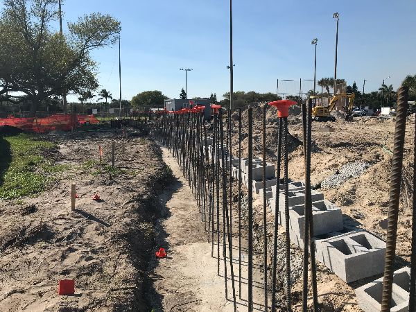 Dirt lot with concrete footer and pieces of line up rebar sticking up straight.