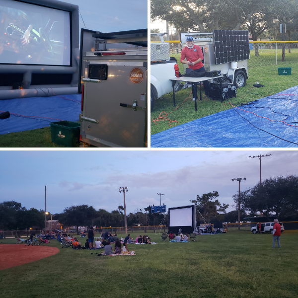 A grassy field with an outdoor movie screen, blankets with families laying on them on the grass     ·         180045 Alt Text: Aaron Leyte working performing audio checks as the Leisure Services department prepares for Movie in the Park.