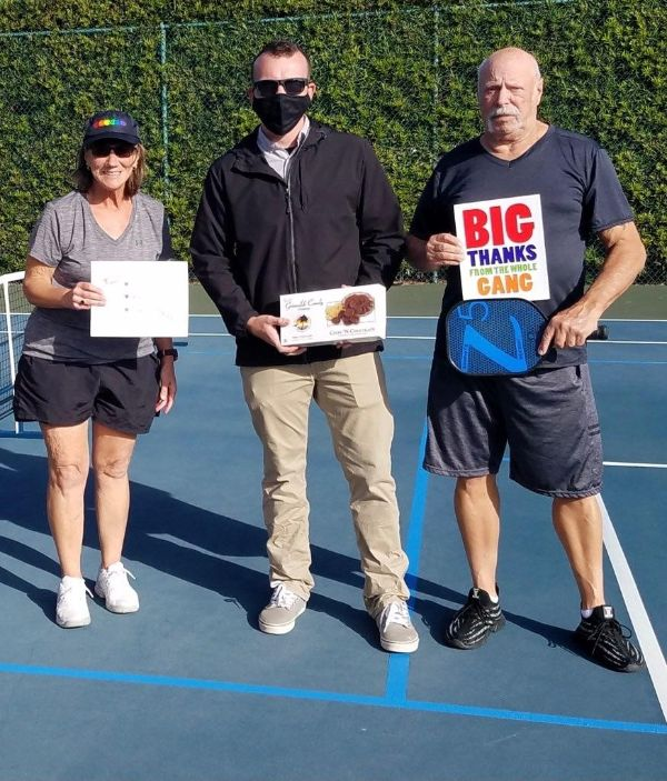 Local players, Janie and Joe, show their gratitude for the newly painted line by presenting staff with a signed thank you card by all the regular pickleball players.