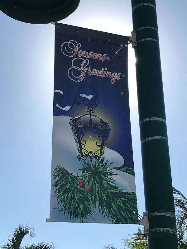 Holiday sign on pole saying Seasons Greetings