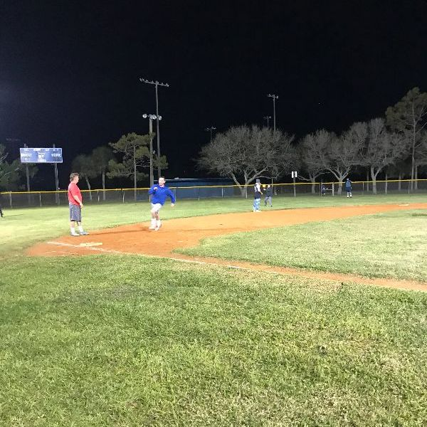 Night kickball game, player rounding third with outfielder throwing ball to infield in the background