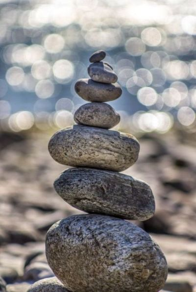 Seven gray stones stacked from large to small, on a soft-focus background of a sandy beach and sparkling water