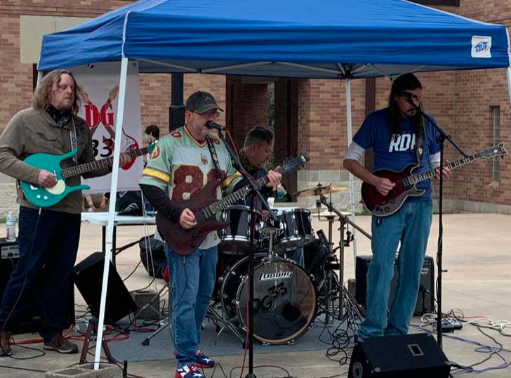 Music band DG33 is performing under a blue canopy tent outdoors.