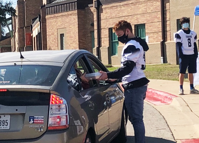 A TSD football player is distributing breakfast in a styrofoam box to a family in a Prius. A teammate can be seen in the background watching.