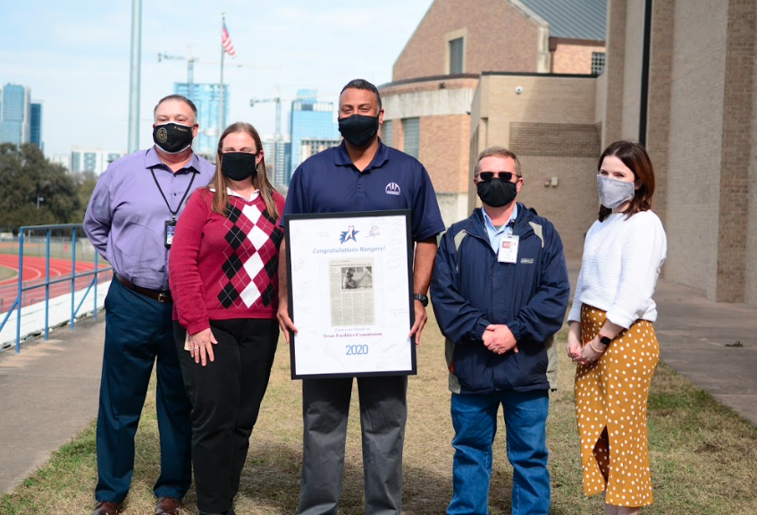 Photo shows five people posing for the camera, all wearing a face mask. From left to right: Marty Martinez, TFC Director of Operations, Beth Polo TSD Support Operations Specialist, TSD Coach John Moore, Nick Sultemeier, TFC Property Management and Supervisor at TSD, and Cassidy Galindo, TFC Warehouse Manager. John Moore is holding a framed gift that showcases the newspaper article about the Rangers winning the state championship for football. On top of it is a picture of the Rangers logo and beneath it is the year 2020.