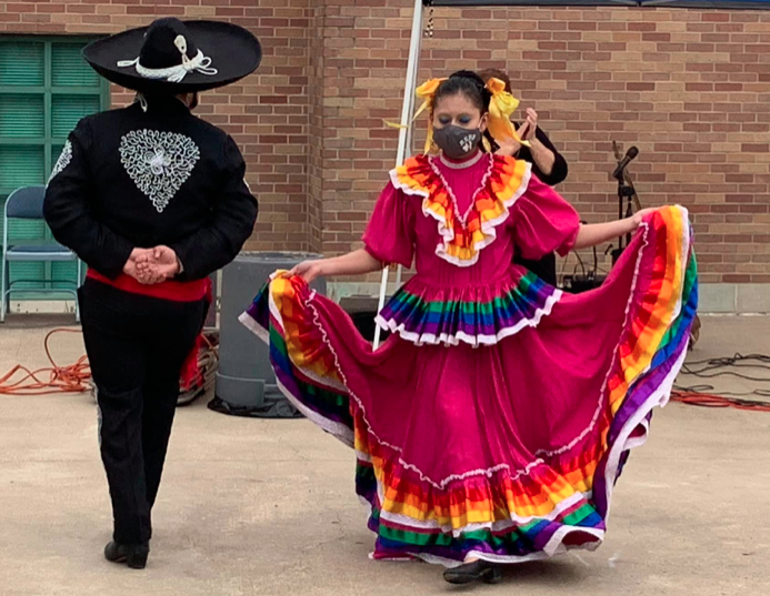 An action shot of a Jalisco dressed woman in a face mask dances, flaring her skirt, while her partner, a traditional mariachi, dances with--his back is towards the camera.