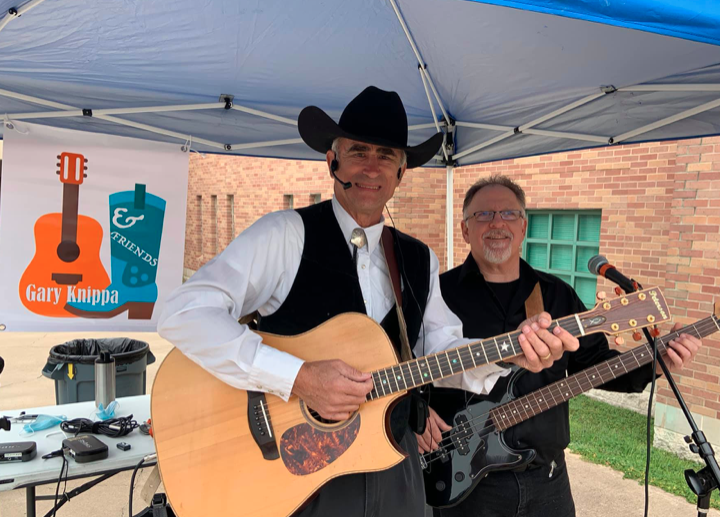 Gary Knippa is performing with his band under a blue canopy tent. Gary Knippa is wearing a black cowboy hat and a black vest. The other person in the photo is wearing a black shirt. Both are holding guitars, smiling towards the camera.