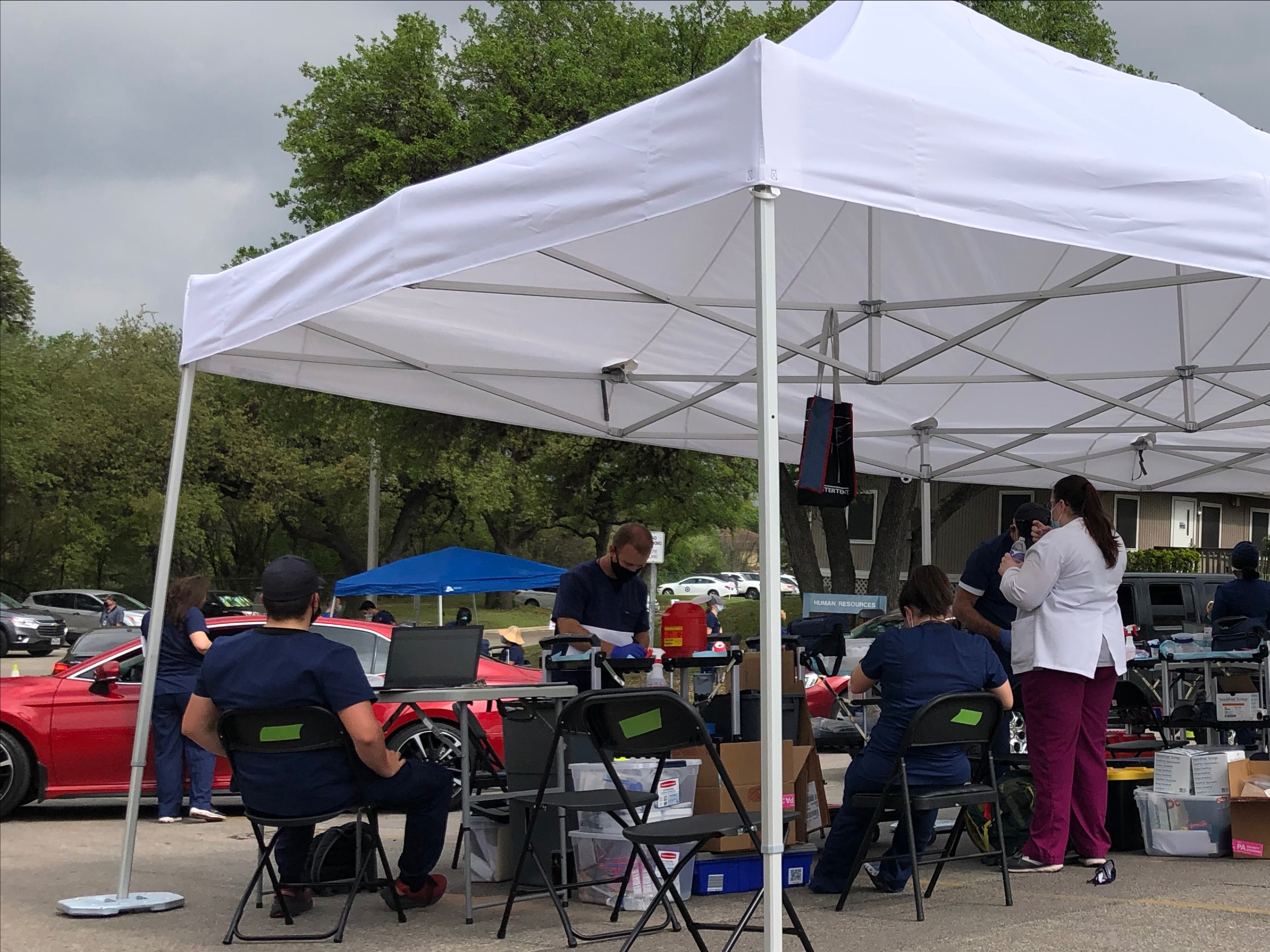 Tarrytown Pharmacy staff and volunteers work under a large, white tent.