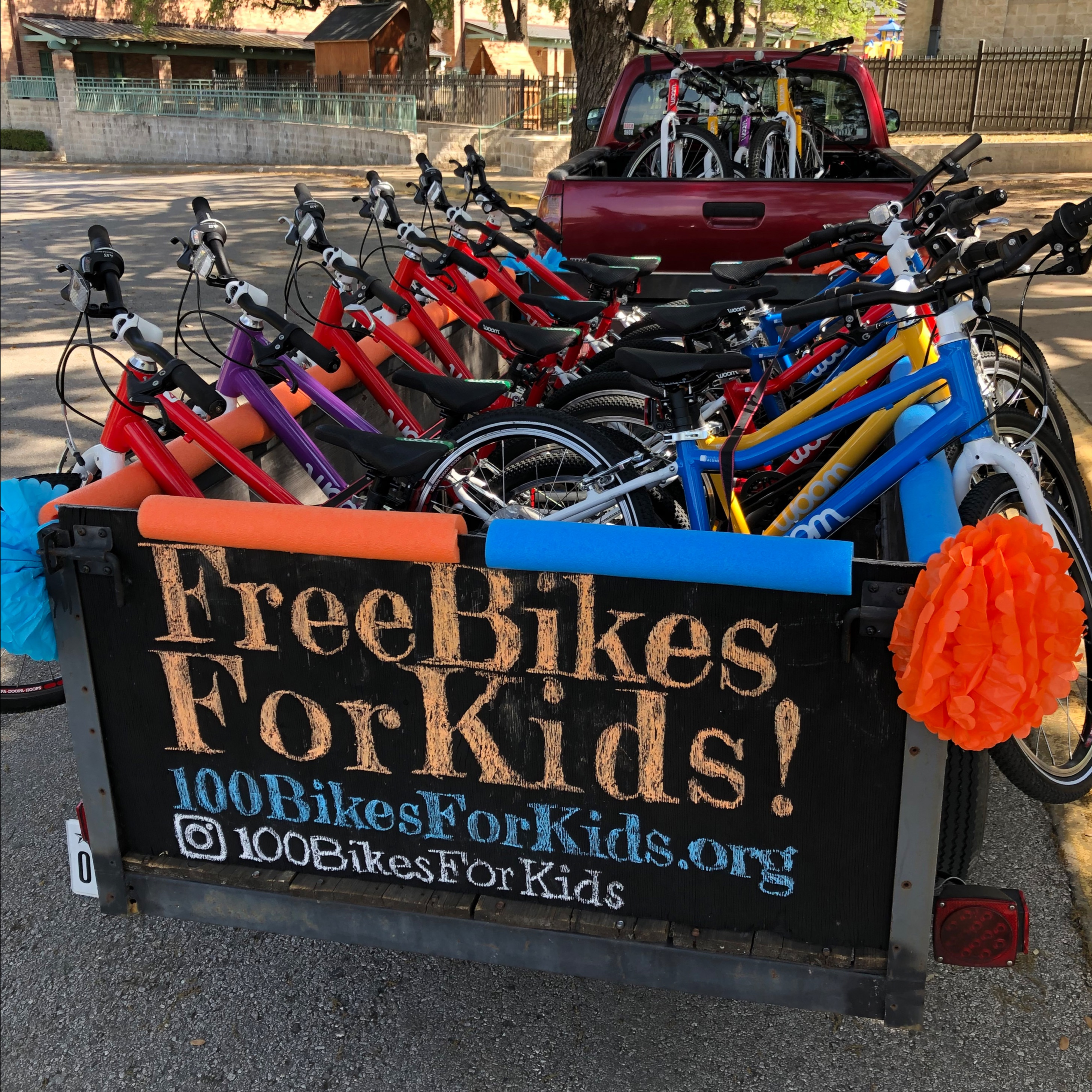 """A maroon truck and trailer is filled with different color woom bikes. The back of the trailer has a sign that reads, """"Free Bikes For Kids! 100BikesForKids.org Instagram 100BikesForKids."""""""