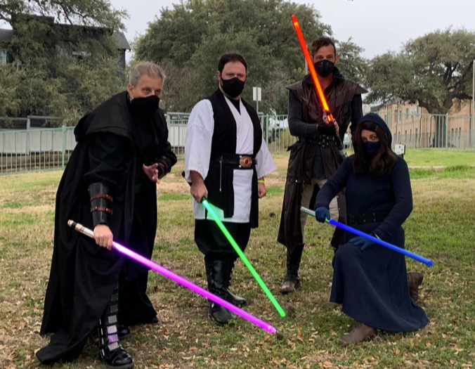 Four Jedis in face masks from The Lone Star Saber Academy pose with their lightsabers.