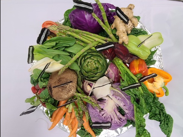 A top-down view of a bowl full of vegetables is shown.  There is a massive pile of carrots, mushroom, ginger, artichoke, asparagus, yellow pepper, red cabbage, spinach, Bok Choy, and more.