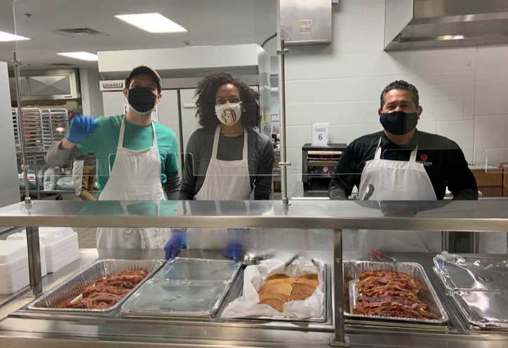 TSD cafeteria workers and volunteers behind the serving line with food in cafeteria trays, ready to serve.