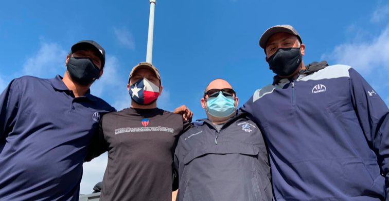 A low angle shot shows TSD Rangers football coaches taking a photo with Share the Will Foundation volunteer. All are huddled together wearing face masks.