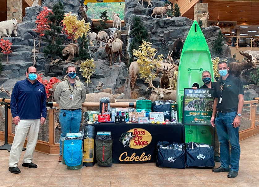 Photo shows Nick Bannon, TSD PE Supervisor, accepting the Outdoor Fund grant from Cabela's and Bass Pro Shop employees, all wearing face masks. The photo also shows a table full of outdoor items in front of a wildlife display.