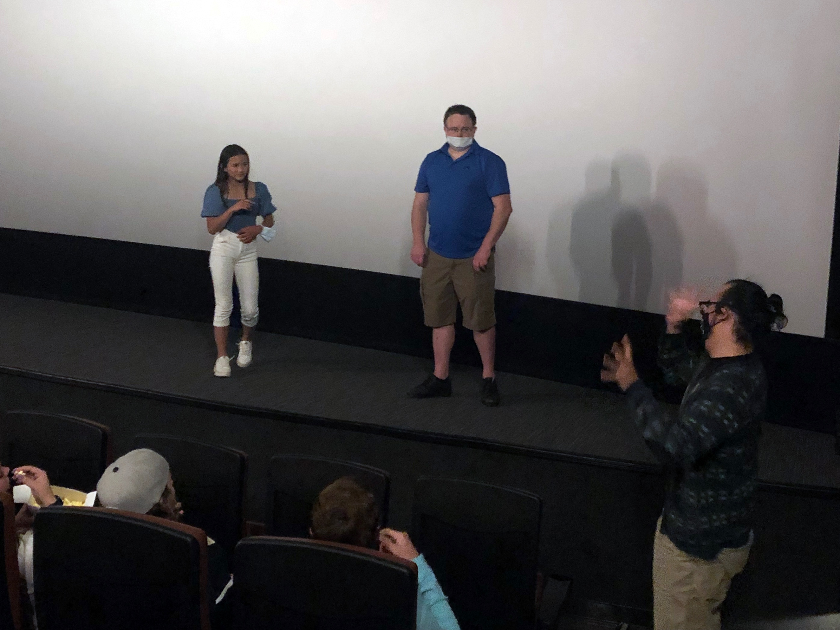 The photo shows Kaylee standing next to her dad Joshua in front of the movie screen at the EVO Entertainment Theater.  There is a man standing off to the side by the first row of movie seats who appears to be asking Kaylee a question.