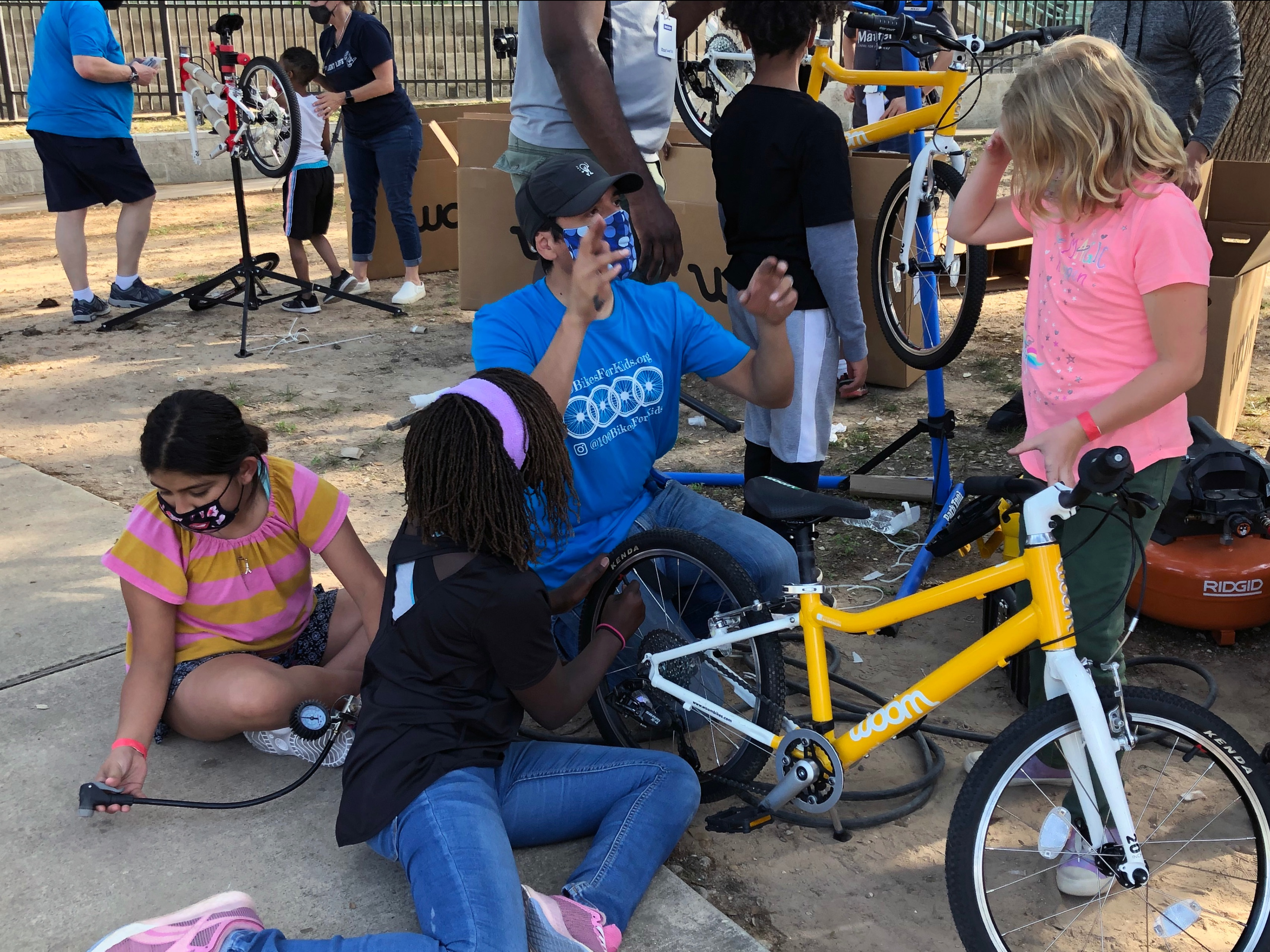 Juan Soto teaches three elementary girls, Julissa S., Zoe T., and McKinzey Y. (left to right) how to assemble a bike.
