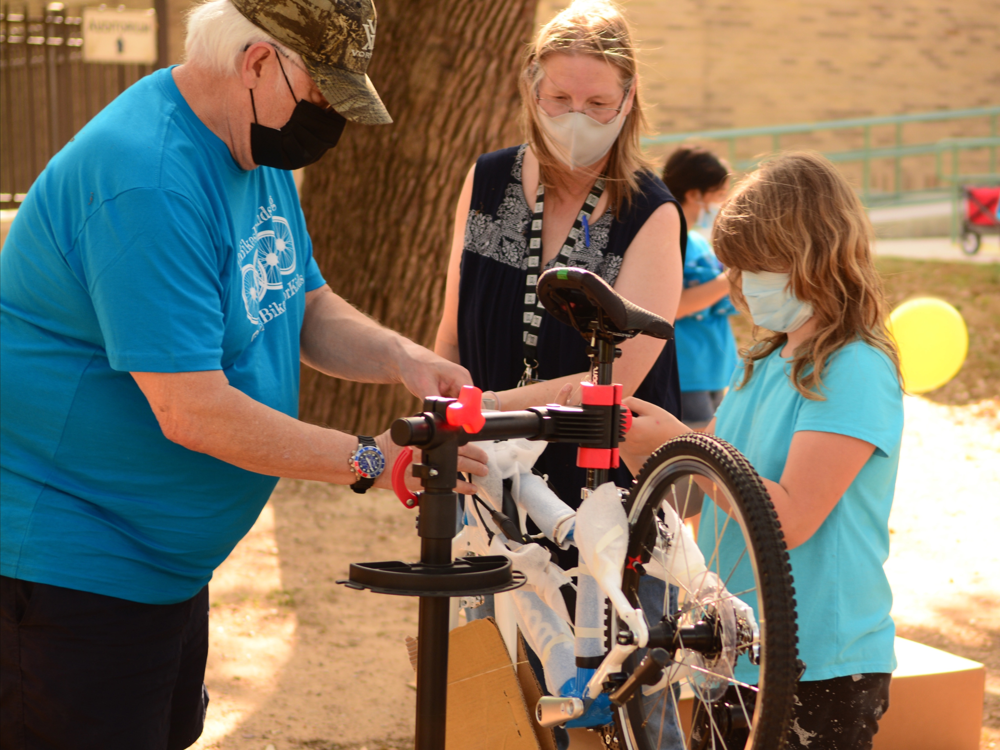 An older man helps a young TSD student, Tessa C., assemble a bike while another woman watches them work.