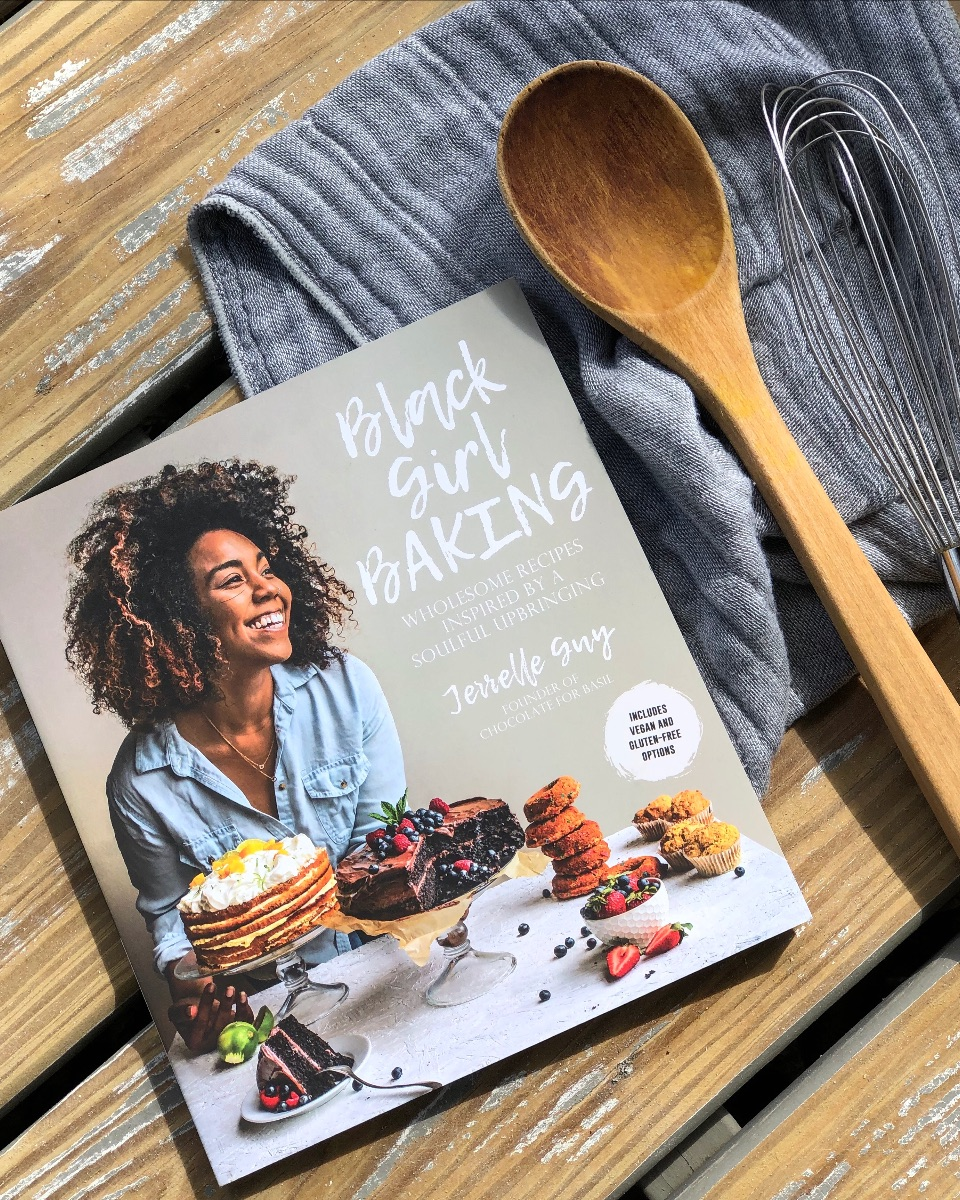Black Girl Baking cookbook, wood spoon, whisk, towel