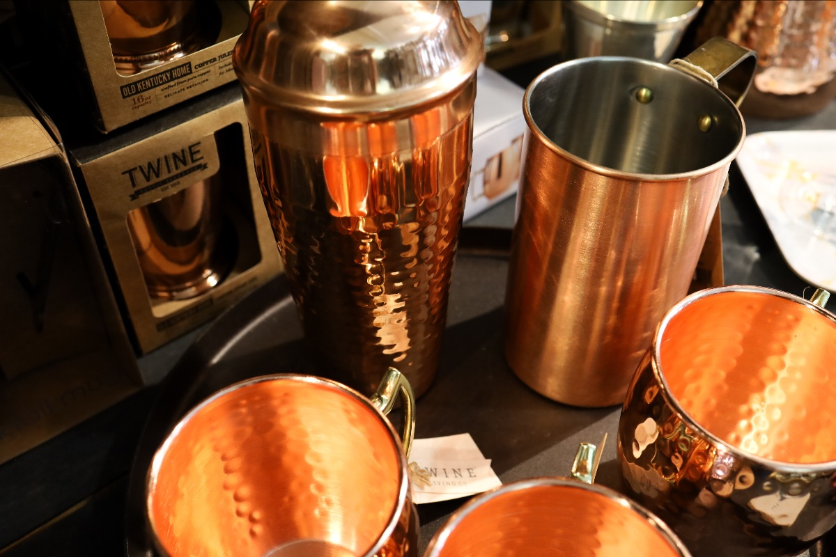 A selection of hammered copper mule mugs and shaker on a spun iron tray