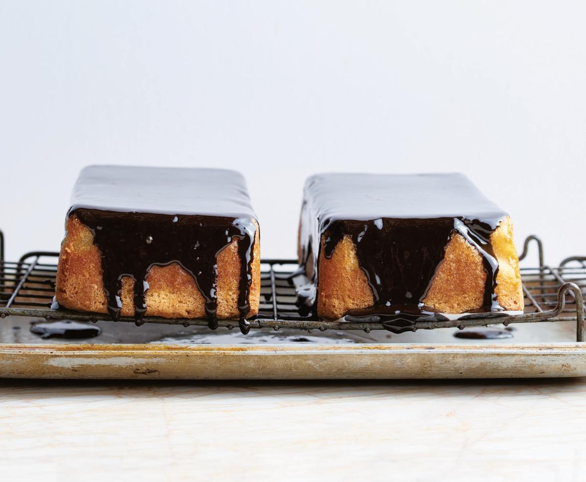 two coconut loaf cakes drizzled with chocolate ganache