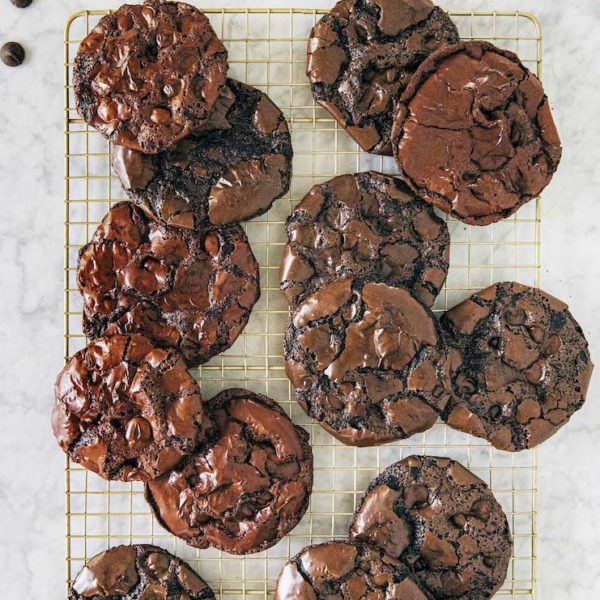 flourless chocolate cookies scattered on gold cooling rack