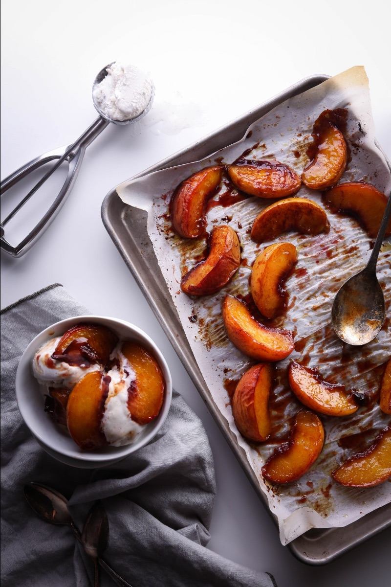 maple roasted peaches on a sheet pan with bowl of ice cream