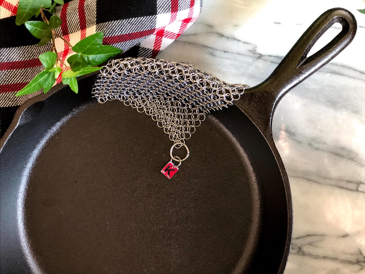 a Knapp Made chain-link scrubber lying over the edge of a cast iron frying pan