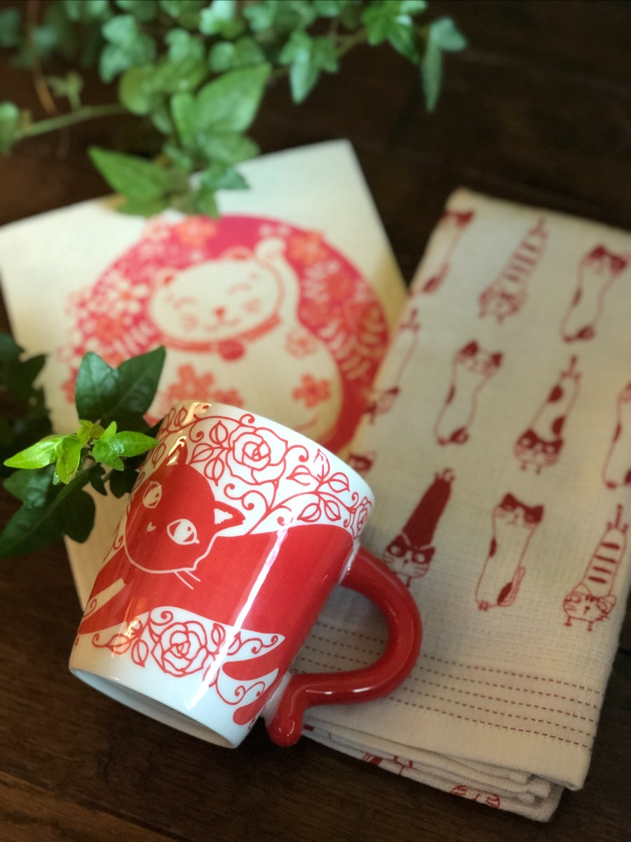 Japanese red cat mug, towel, and Swedish lucky cat dish cloth