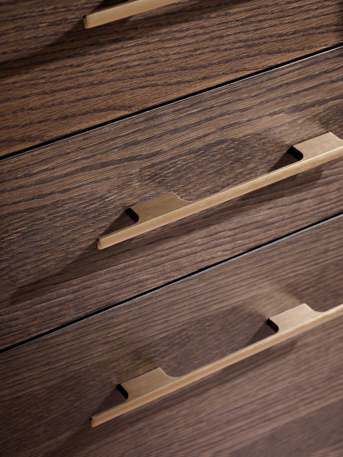 Úchytka TAU v rozteči 286mm a povrchové úpravě broušená mosaz aplikovaná na dřevěný nábytek.