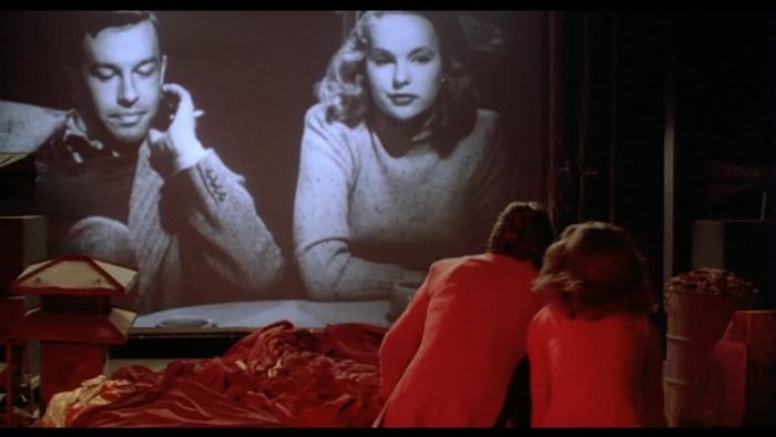 A couple lit in red watching a black and white movie