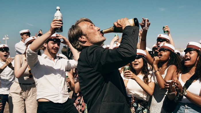 Actor Mads Mikkelsen drinking from a champagne bottle